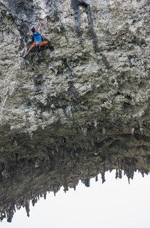 Low angle view of male climber climbing the route Lunatic on Moon Hill in Yangshuo, Guangxi Zhuang, China - CUF29859