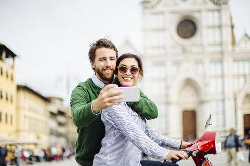 Young couple taking smartphone selfie in front of Basilica di Santa Croce, Florence, Italy - CUF29874