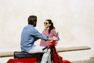 Young couple on moped chatting, Florence, Italy - CUF29883
