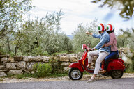 Young couple on moped pointing at olive grove, Florence, Italy - CUF29889