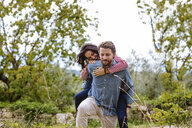Young man giving girlfriend a piggy back in olive grove, Florence, Italy - CUF29892