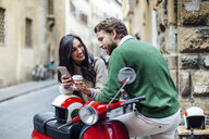 Young couple leaning on moped reading smartphone texts, Florence, Italy - CUF29898
