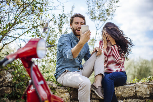 Young couple sitting on olive grove wall reading smartphone, Florence, Italy - CUF29904