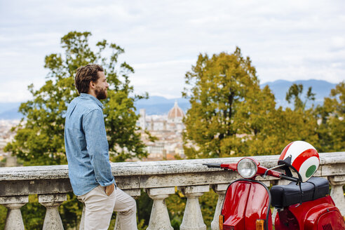 Young man looking at view from San Miniato church, Florence, Italy - CUF29907