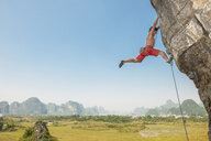 Male climber hanging from the Egg - a limestone cliff in Yangshuo, Guangxi Zhuang, China - CUF29952