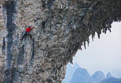 Male climber climbing on Moon Hill - a limestone cliff in Yangshuo, Guangxi Zhuang, China - CUF29955