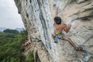 Male climber climbing at white Mountain - a limestone cliff in Yangshuo, Guangxi Zhuang, China - CUF29961