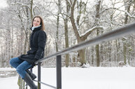 Side view of mid adult woman in snow covered park sitting on railings looking at camera smiling, Munich, Germany - CUF29964