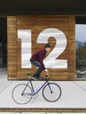 Urban cyclist balancing on bicycle in front of numbered wooden wall - CUF29973