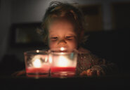 Surface level view of preschool girl looking down at burning candles - CUF29991