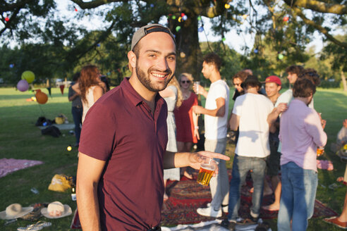 Portrait of young man at crowded party in park at sunset - CUF30006