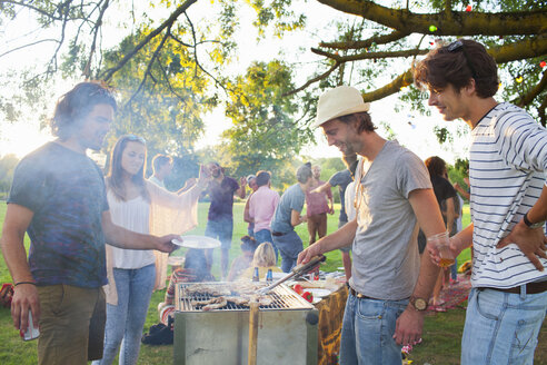 Happy adult friends barbecuing at sunset party in park - CUF30009