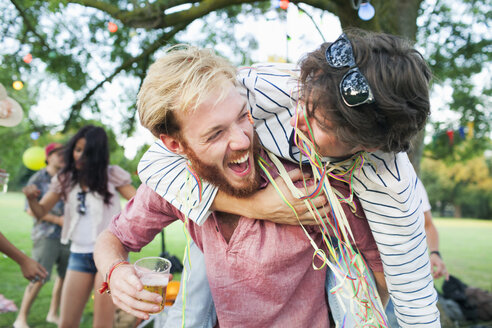 Two male adult friends wrapped in streamers hugging at sunset party in park - CUF30015