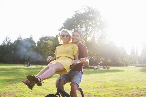 Portrait of young couple having fun on bicycle at sunset party in park - CUF30024