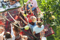 Overhead view of group of friends relaxing on rug at sunset park party - CUF30030