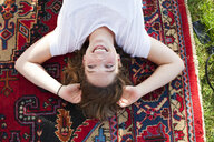 Overhead view of young woman lying back on rug - CUF30042