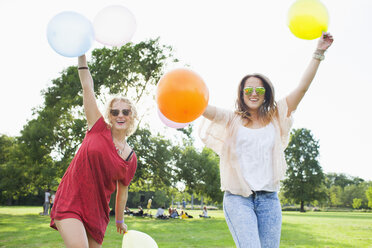 Portrait of two young women dancing with balloons at park party - CUF30045