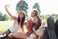 Female friends taking smartphone selfie at park party - CUF30054