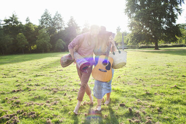 Romantic young couple carrying rug in park - CUF30057