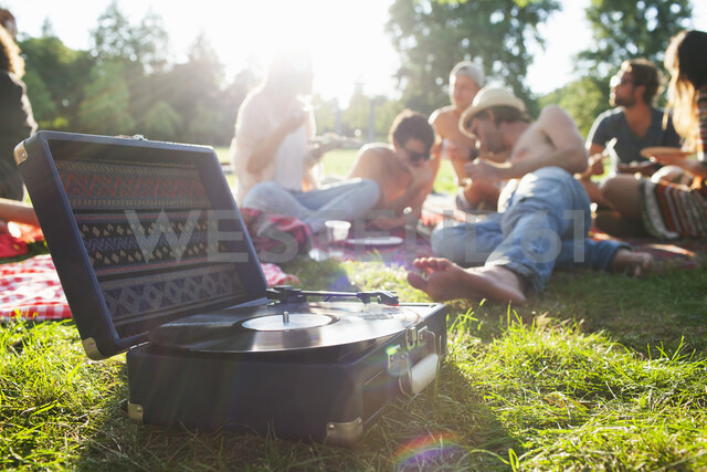 Adult friends relaxing and listening to record deck at sunset park party - CUF30066