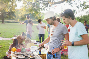 Young men barbecuing at group party in park - CUF30078