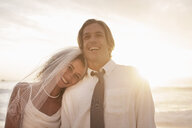 Bride leaning on groom's shoulder on beach against sunset - CUF30096
