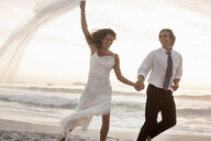 Bride and groom running on beach against sunset - CUF30099