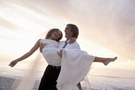 Groom carrying bride on beach against sunset - CUF30102