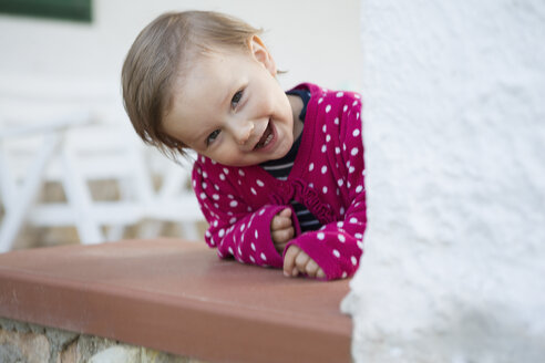 Portrait of female toddler leaning forward and peeking from table - CUF30114