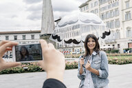 Young woman holding umbrella posing for friend using smartphone to take photograph, Piazza Santa Maria Novella, Florence, Tuscany, Italy - CUF30153