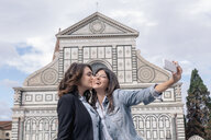 Lesbian couple using smartphone to take selfie in front of church, kiss on cheek, Piazza Santa Maria Novella, Florence, Tuscany, Italy - CUF30159