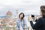 Young woman posing for friend taking photograph in front of Florence Cathedral and Giotto's Campanile looking over shoulder smiling, Florence, Tuscany, Italy - CUF30162