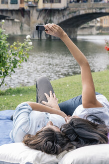 Lesbian couple lying down using smartphone to take selfie in front of Ponte Vecchio over river Arno, Florence, Tuscany, Italy - CUF30168