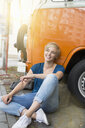 Young woman sitting cross legged leaning against campervan - CUF30195