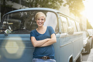 Portrait of young woman leaning against parked campervan - CUF30198