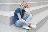 Happy young woman wearing headphones sitting on city stairway - CUF30204