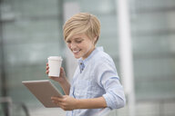 Young woman reading digital tablet whilst drinking takeaway coffee - CUF30219