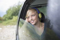 Young woman wearing headphones looking out of open car window - CUF30222