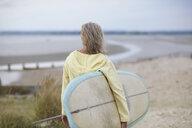 Senior woman walking towards beach, carrying surfboard, rear view - CUF30249