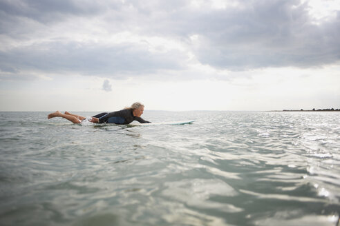 Senior woman on surfboard in sea, paddleboarding - CUF30255