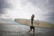 Senior woman walking from sea, carrying surfboard - CUF30258