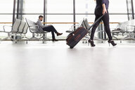 Woman on the move through departure lounge with suitcase - CUF30500