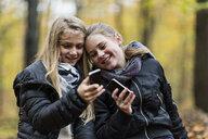 Girls using smartphone in autumn forest - CUF30527