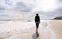 Mature woman, walking along beach, rear view - CUF30536