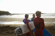 Group of surfers standing on beach, holding surfboards, rear view - CUF30656