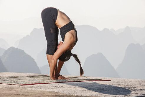 Side view of woman bending over in yoga pose above limestone mountains, Yangshuo, Guangxi Zhuang, China - CUF30665