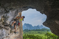 Female climber climbing at the Egg in Yangshuo, Guangxi Zhuang, China - CUF30671