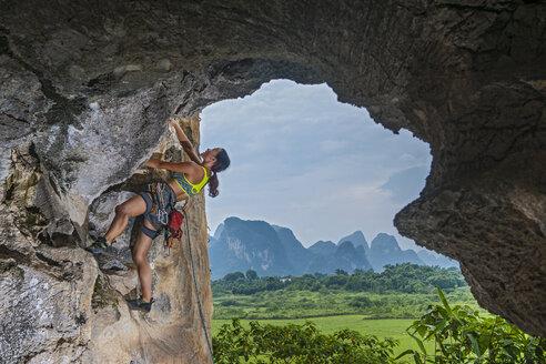 Female climber climbing at the Egg in Yangshuo, Guangxi Zhuang, China - CUF30671