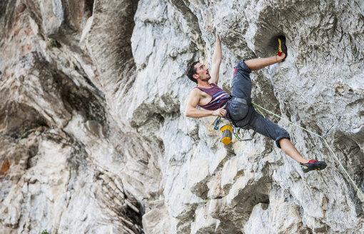 Male climber at Riverside crag in Yangshuo, Guangxi Zhuang, China - CUF30680