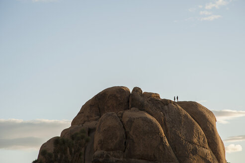 Two people on high rock formation, Joshua Tree national park, California, USA - CUF30704